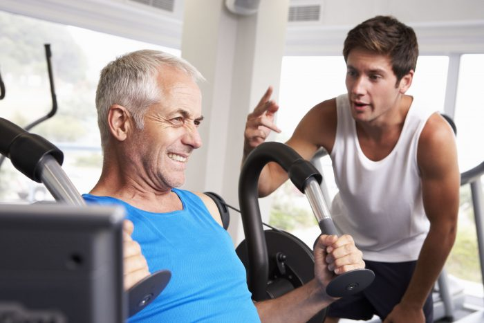 42249652 - middle aged man being encouraged by personal trainer in gym